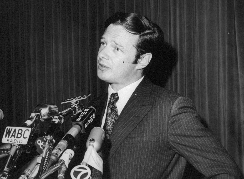 Brian Epstein surrounded by microphones