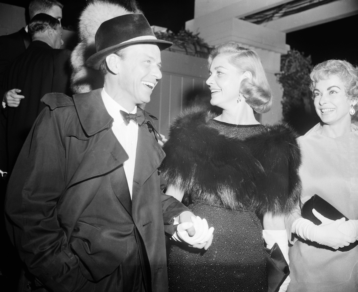 Frank Sinatra and Lauren Bacall holding hands