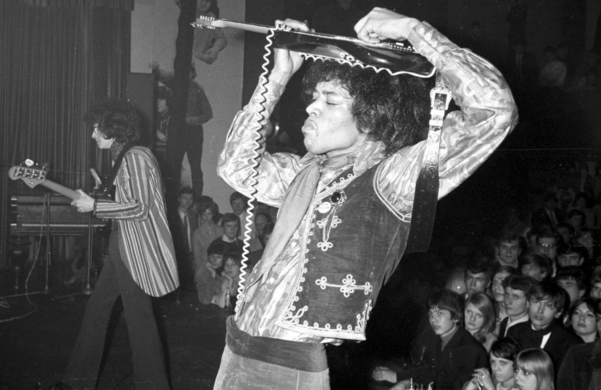 Hendrix playing guitar on top of his head