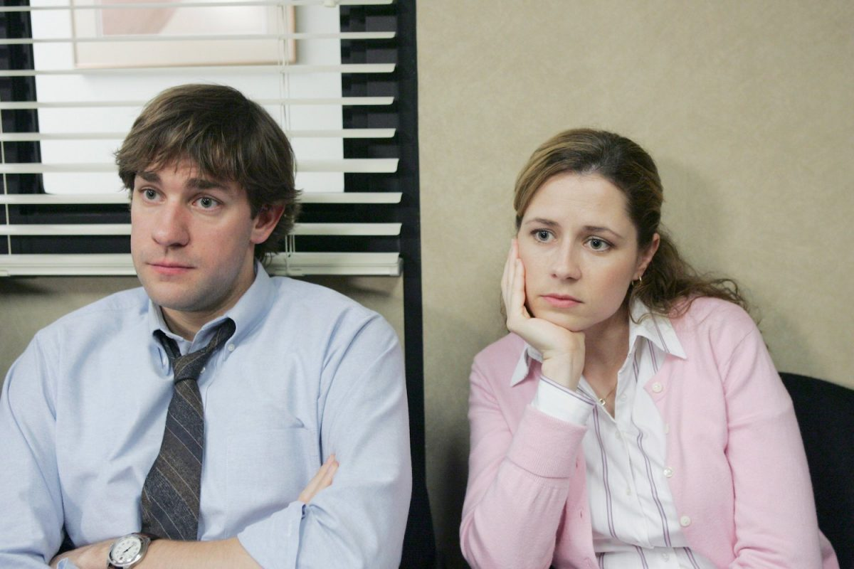 The Office stars John Krasinski as Jim Halpert and Jenna Fischer as Pam Beesly sit next to each other in the conference room
