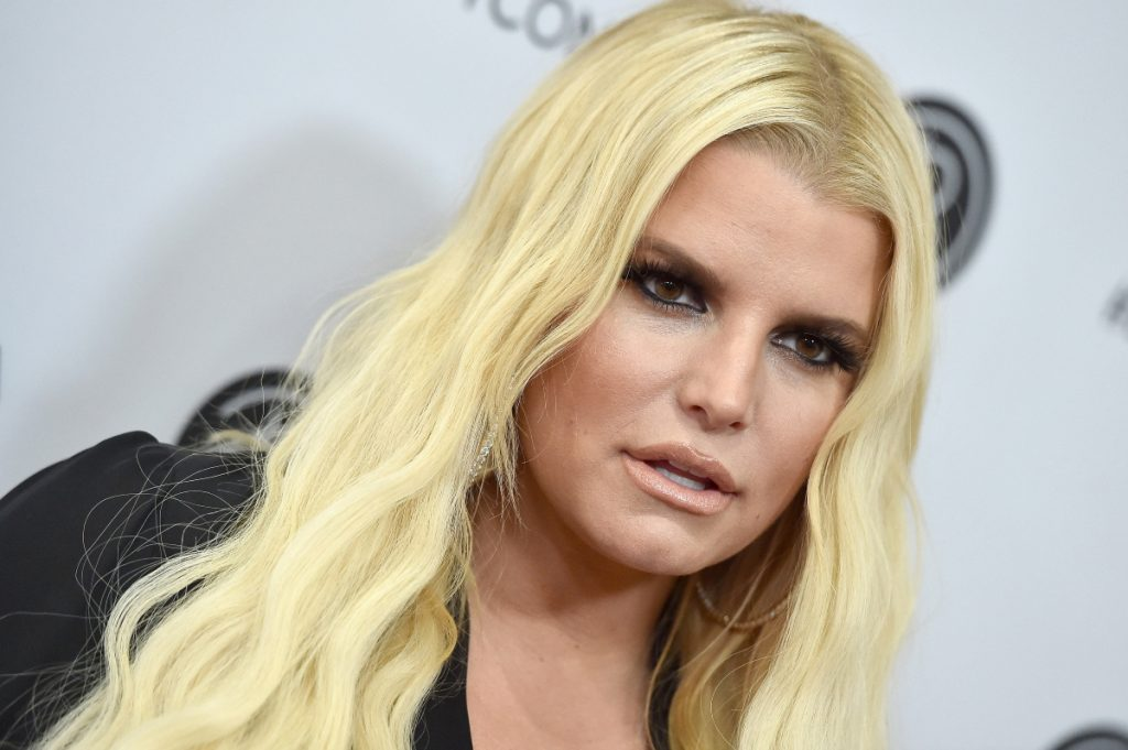Closeup of Jessica Simpson looking on in front of a gray backdrop
