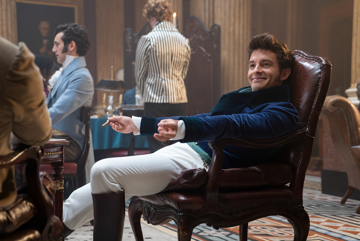Smiling Anthony Bridgerton (Jonathan Bailey) wearing white pants and blue jacket sitting in a chair.