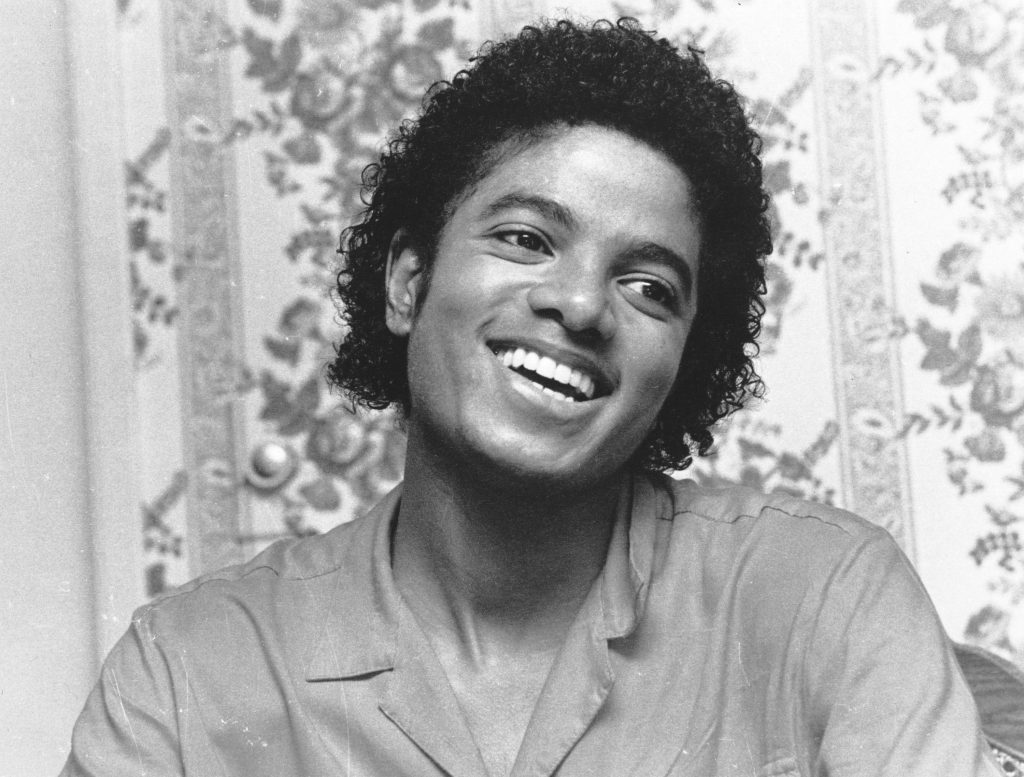 Michael Jackson in front of a wall with wallpaper on it