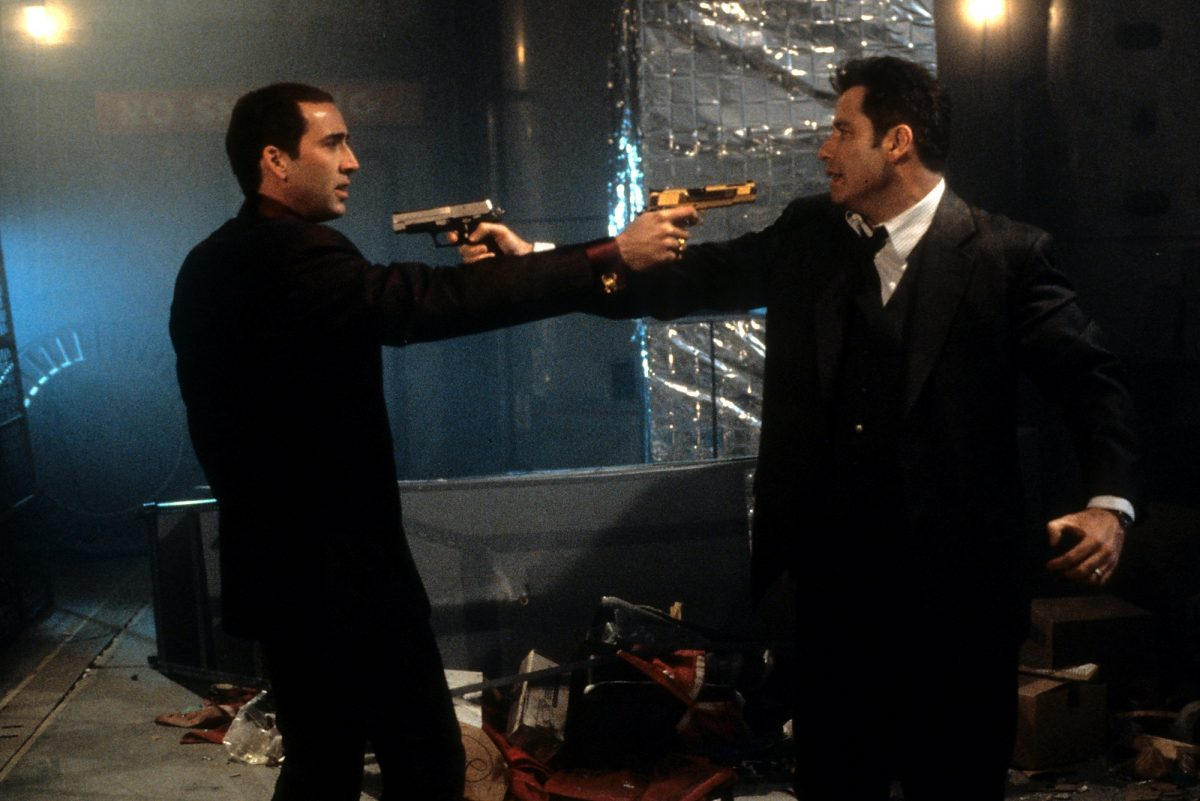 Face/Off stars Nicolas Cage and John Travolta point guns at each other