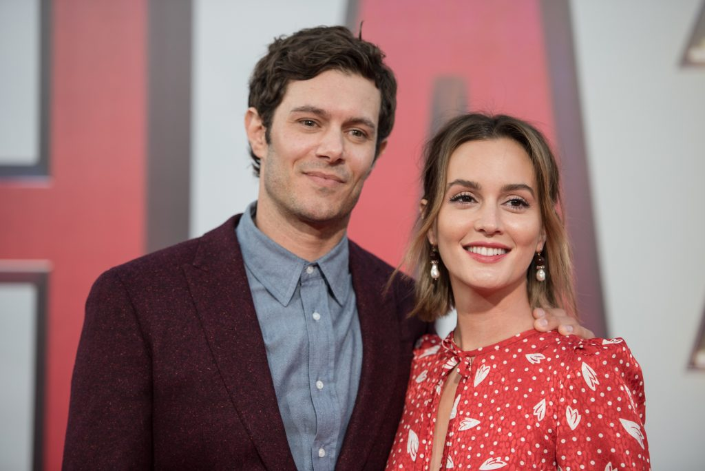 (L-R) Adam Brody and Leighton Meester smiling in front of a blurred background