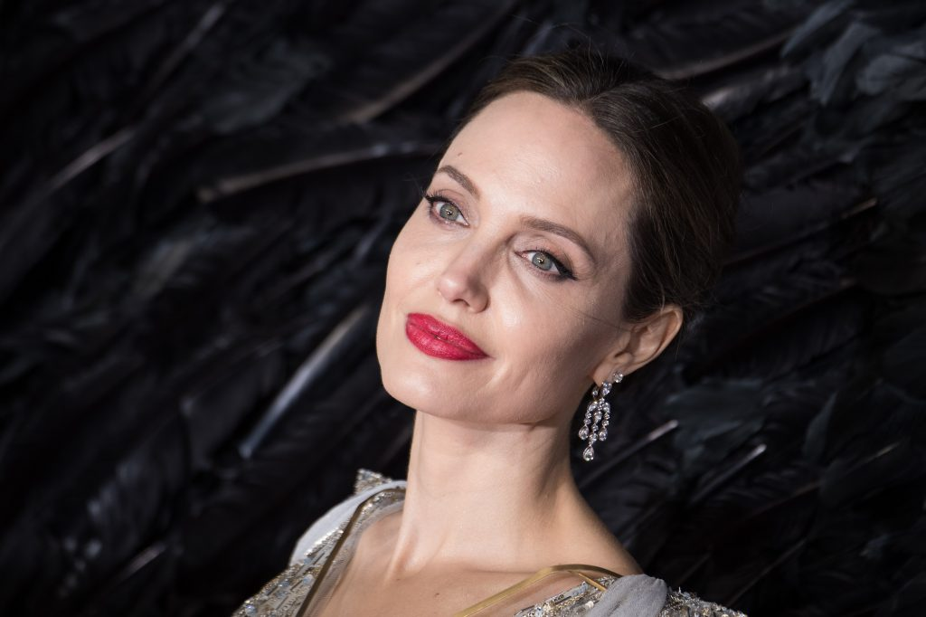 Angelina Jolie smiling in front of a black background