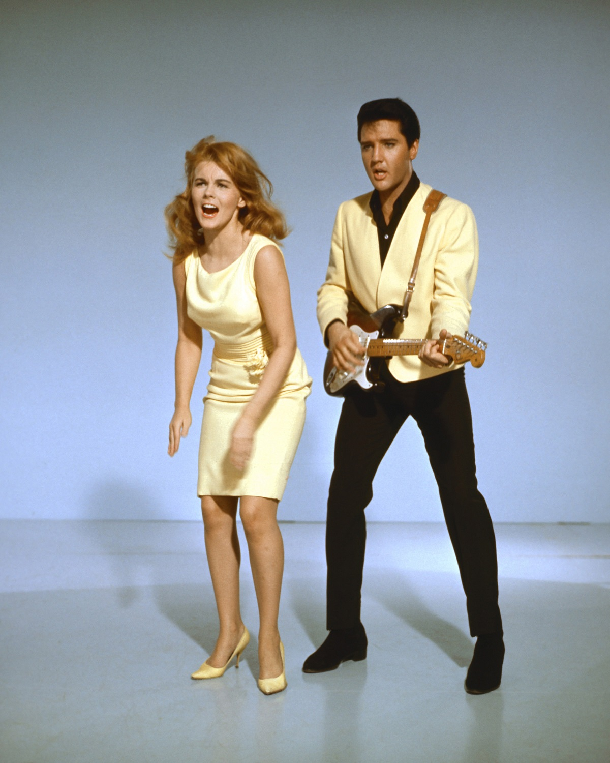 Elvis Presley with a guitar and Ann-Margret singing in a publicity shot for 'Viva Las Vegas'