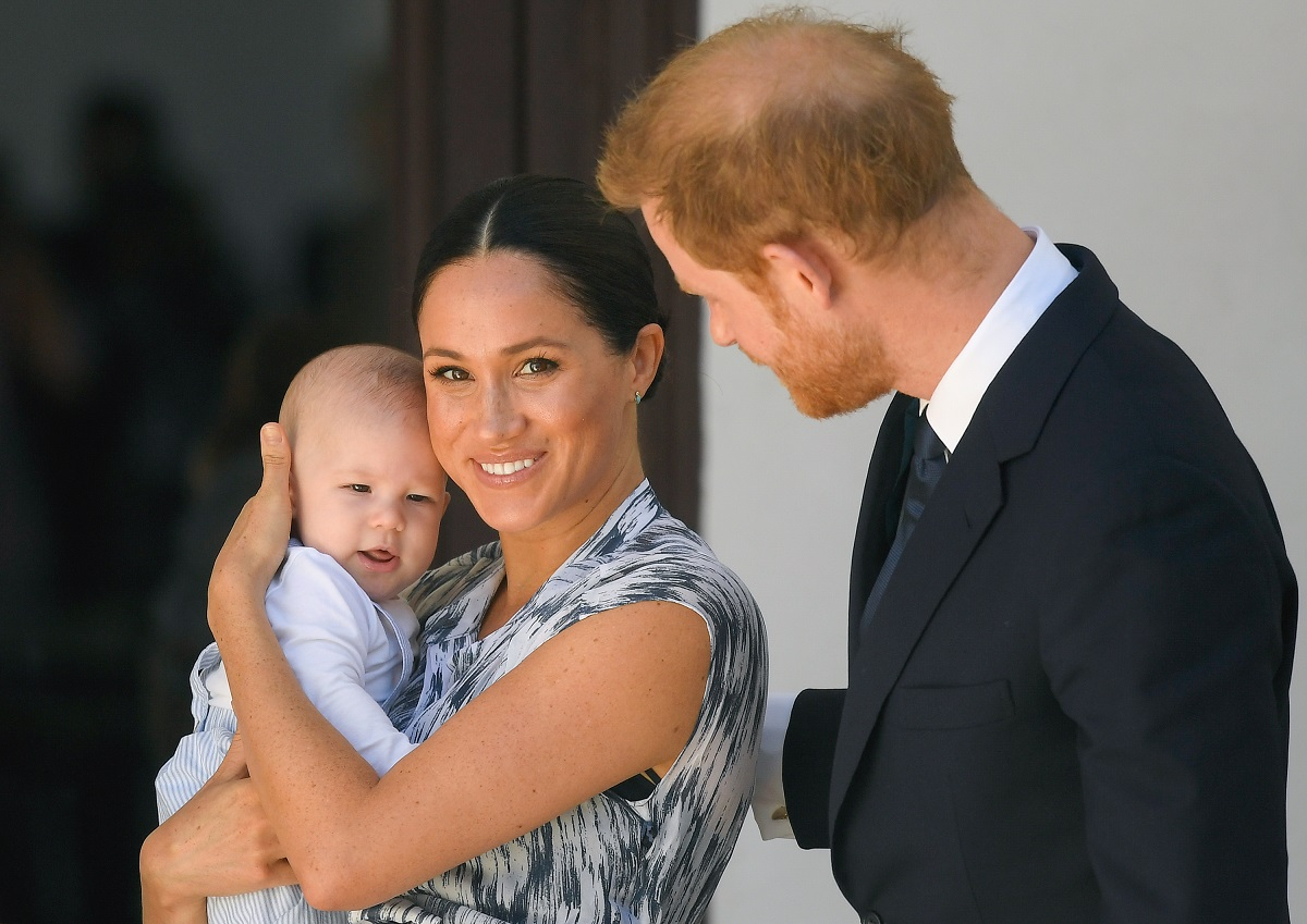 Prince Harry, Duke of Sussex, and Meghan, Duchess of Sussex, with baby Archie during their royal tour of South Africa in Cape Town; Meghan is smiling at the camera and holding Archie.