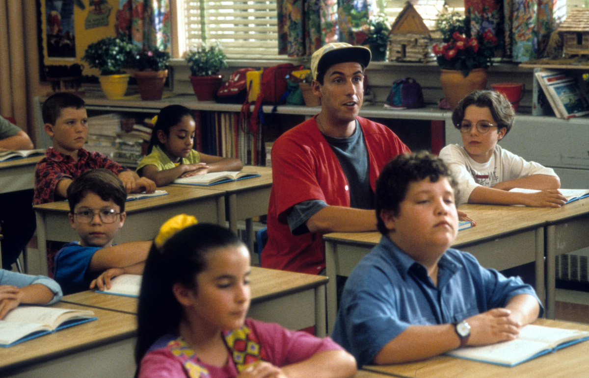 Adam Sandler sitting at a desk in a class for children in a scene from the film 'Billy Madison'