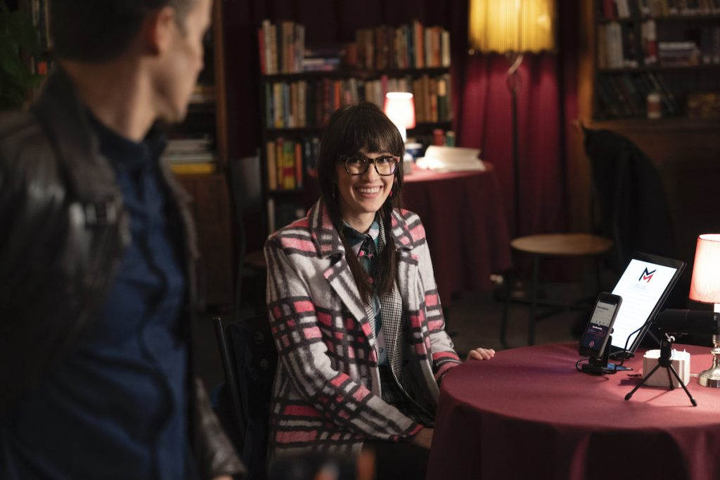 Jamie Reagan is opening a door and looking back at Alison Gable, who is sitting down at a table on 'Blue Bloods'