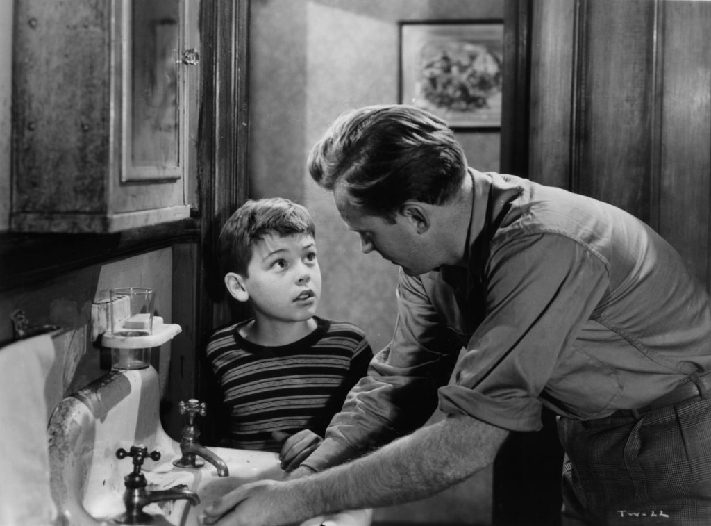 Bobby Driscoll looking up at Arthur Kennedy in a scene from the film 'The Window' in black and white