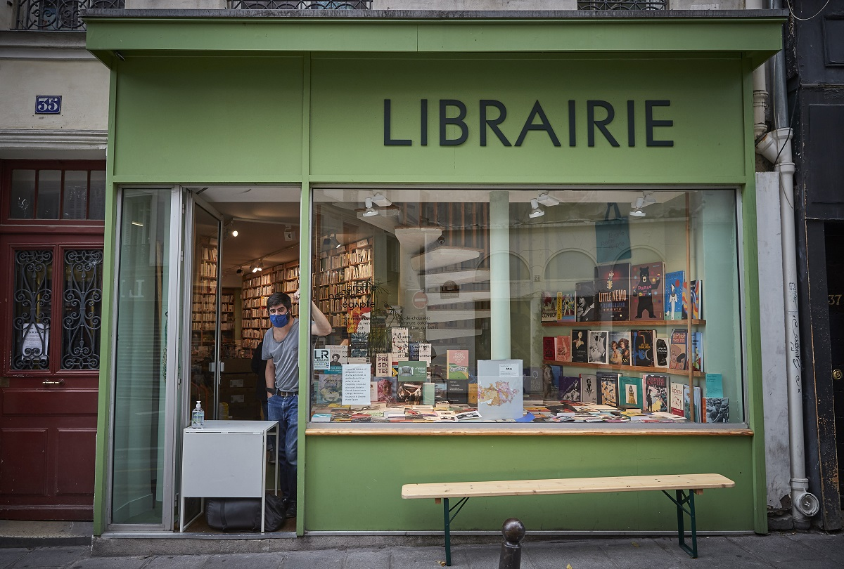 The street view of a glass-windowed bookshop in Paris named 'Librarie.' The storefront is green. A customer in a mask is inside the store.