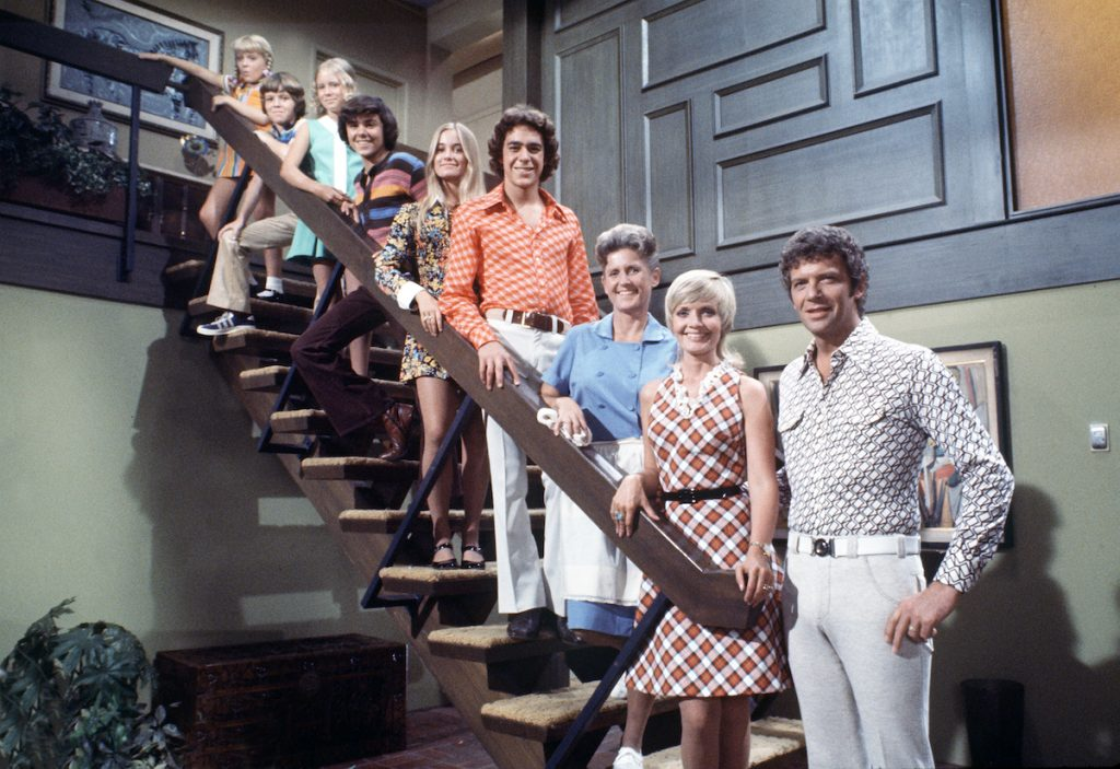 'The Brady Bunch' cast stands on the staircase of their living room set