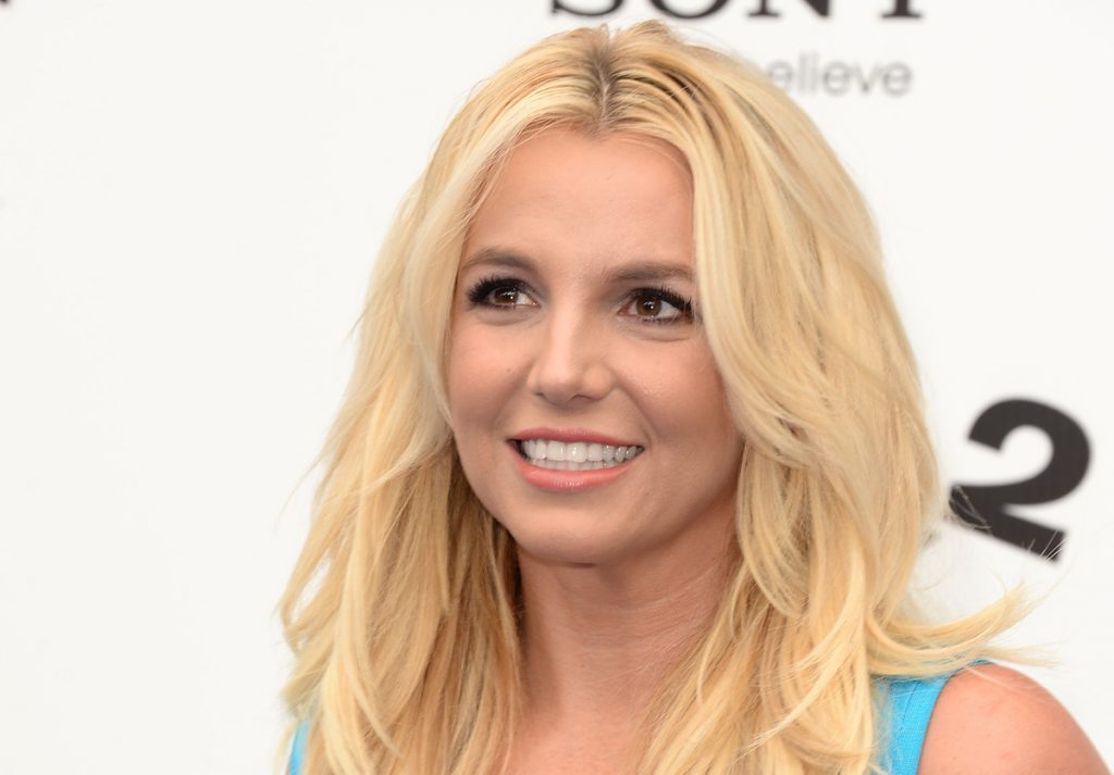 Britney Spears smiling while looking to the left wearing a turquoise top.