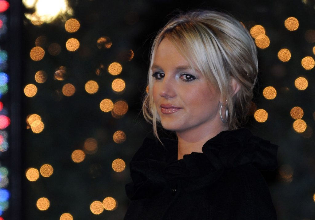 Britney Spears headshot with her wearing black and her hair tied up with bangs framing her face.