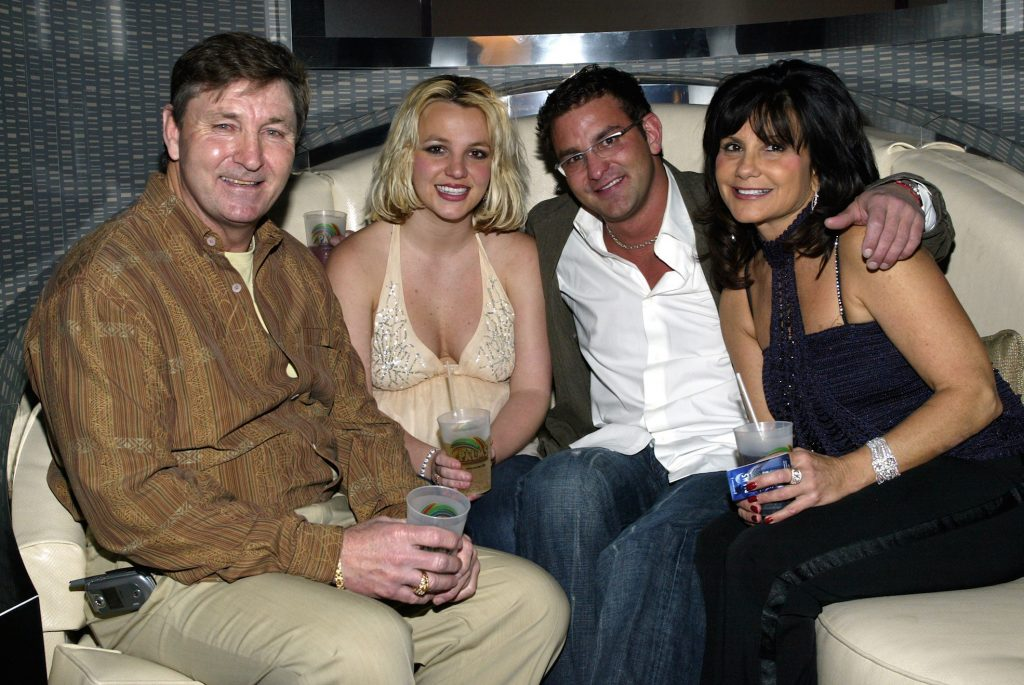 Britney Spears sitting and smiling with father Jamie Spears, brother Bryan Spears, and mother Lynne Spears