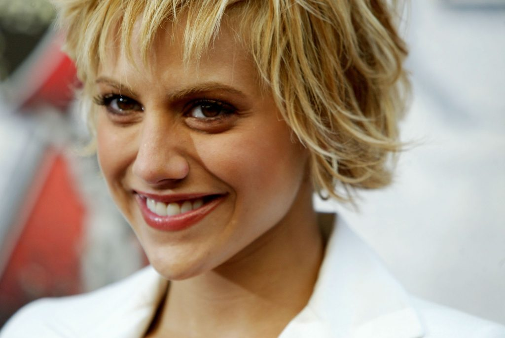 Brittany Murphy smiling in front of a blurred background