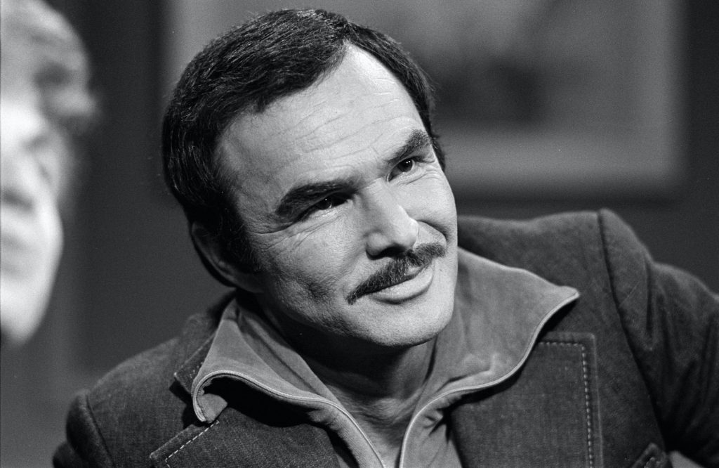 Burt Reynolds smiling, head tilted, in black and white