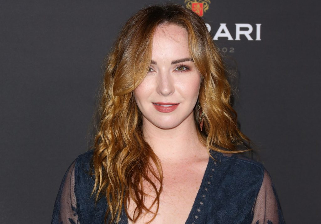Camryn Grimes smiling in front of a gray background