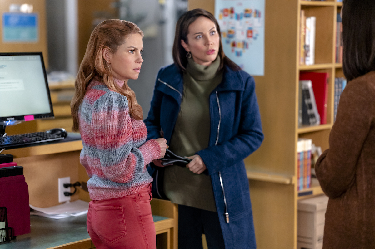Candace Cameron Bure as Aurora Teagarden and Lexa Doig looking confused in a library