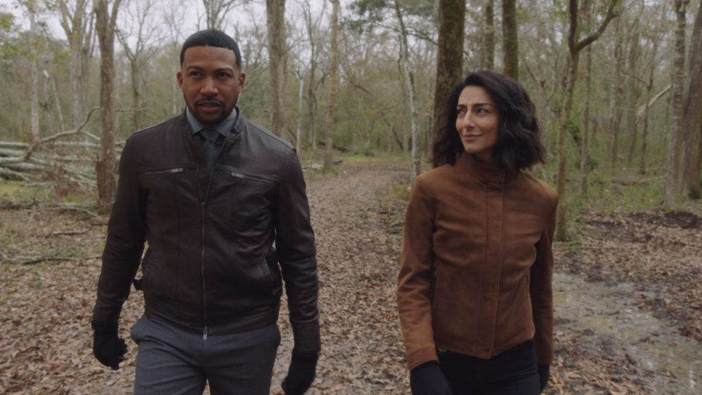 Charles Michael Davis as Special Agent Quentin Carter and Necar Zadegan as Special Agent Hannah Khoury walk in the woods