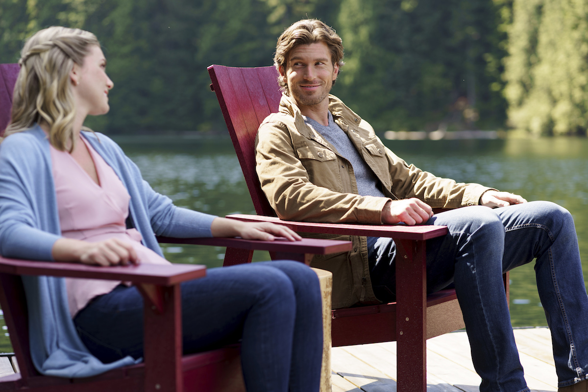 Man and woman sitting in red Adirondack chairs on a dock with lack in background