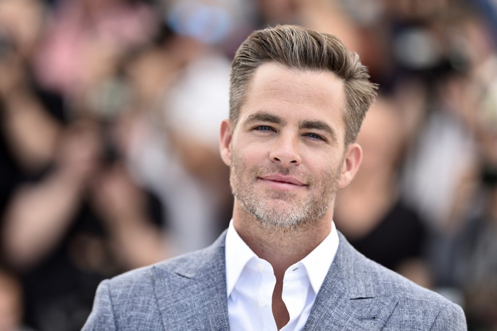 Chris Pine headshot at a red carpet event outdoors. He is wearing a gray suit.