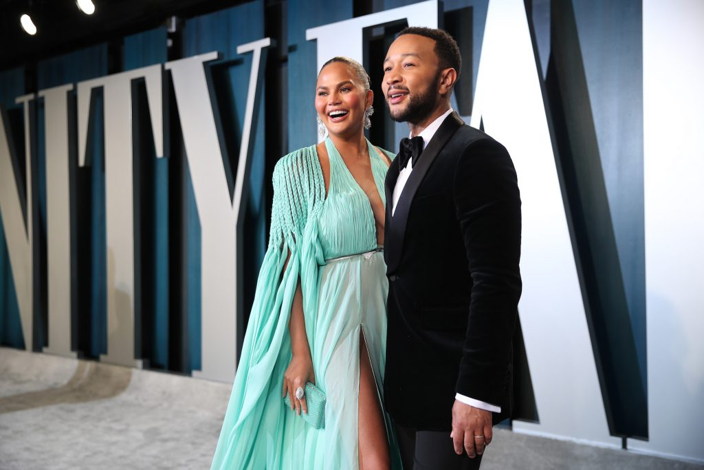 (L-R) Chrissy Teigen and John Legend smiling in front of a blue and white background on an awards show carpet