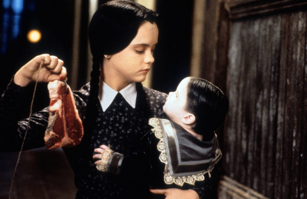 Christina Ricci as Wednesday Addams dangling meat in front of a baby in the movie 'Addams Family Values'