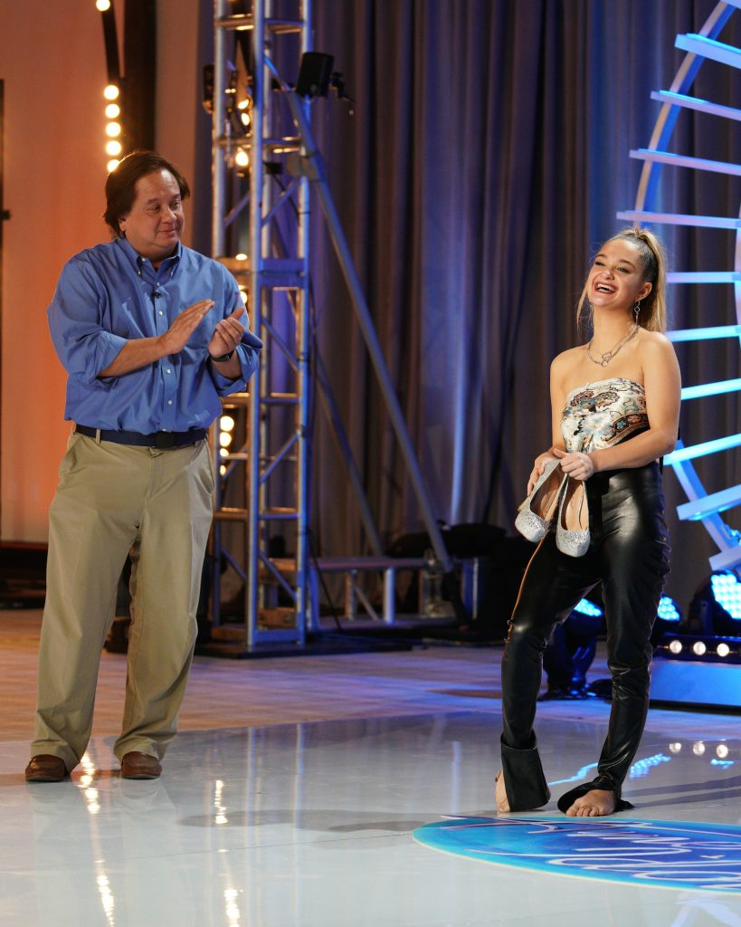 Claudia Conway standing and laughing next to her father on the 'American Idol' stage