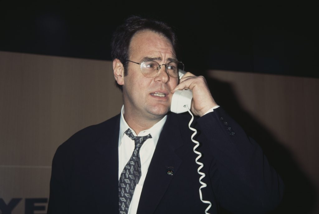 Dan Aykroyd turned to the side, on a corded phone