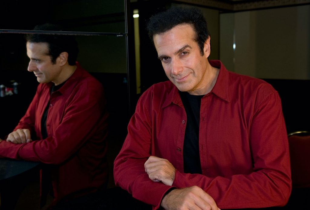 David Copperfield smiling at the camera to the right of a mirror