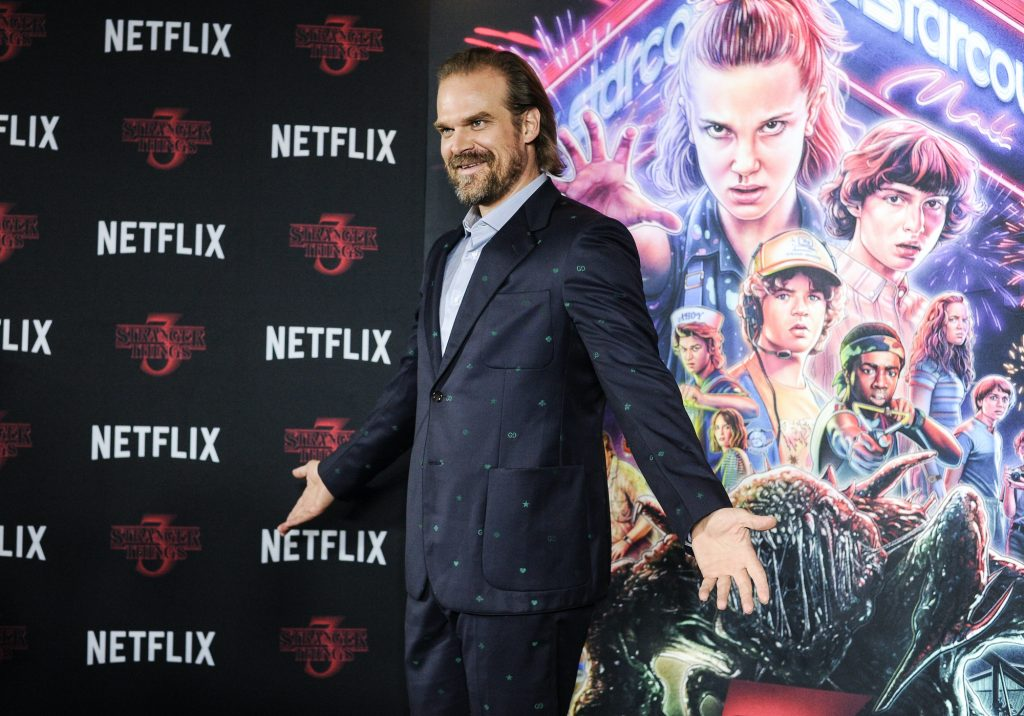 David Harbour smiling, arms outstretched, in front of a 'Stranger Things' poster