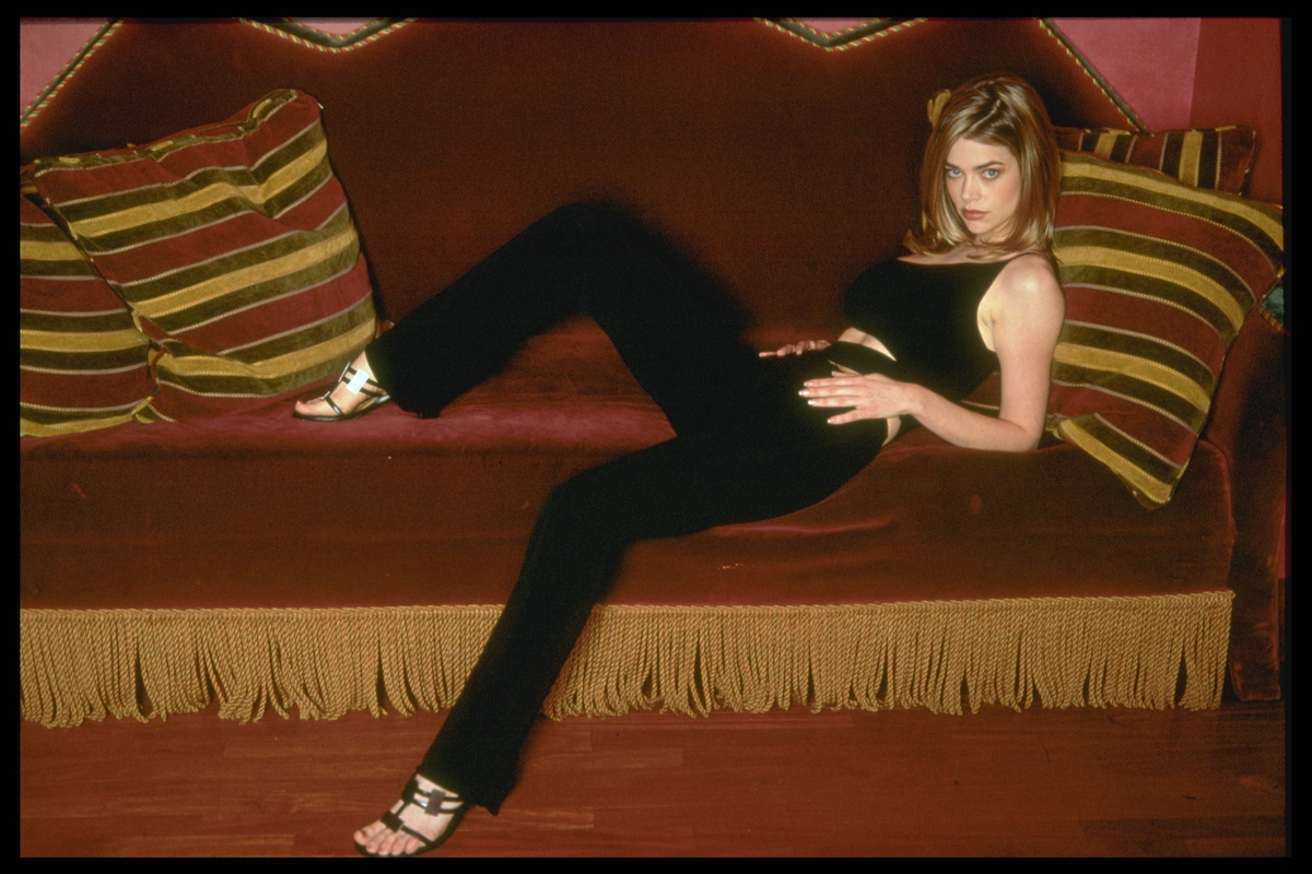 Denise Richards poses on a couch