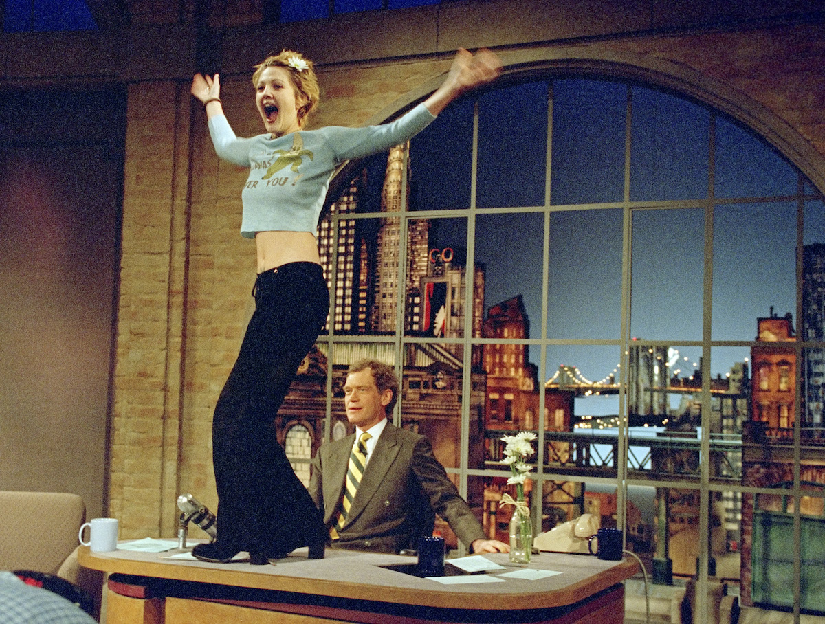 Drew Barrymore turns to the audience after flashing host David Letterman on 'The Late Show with David Letterman' in 1995