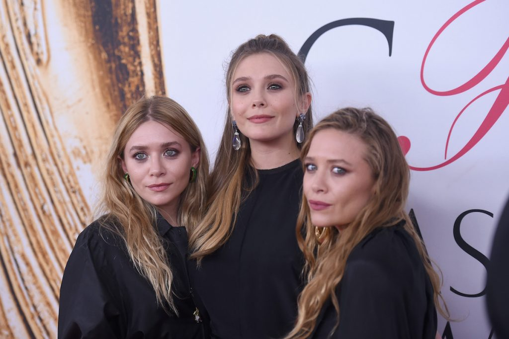 Elizabeth Olsen with her sisters Mary-Kate and Ashley Olsen at a red carpet event
