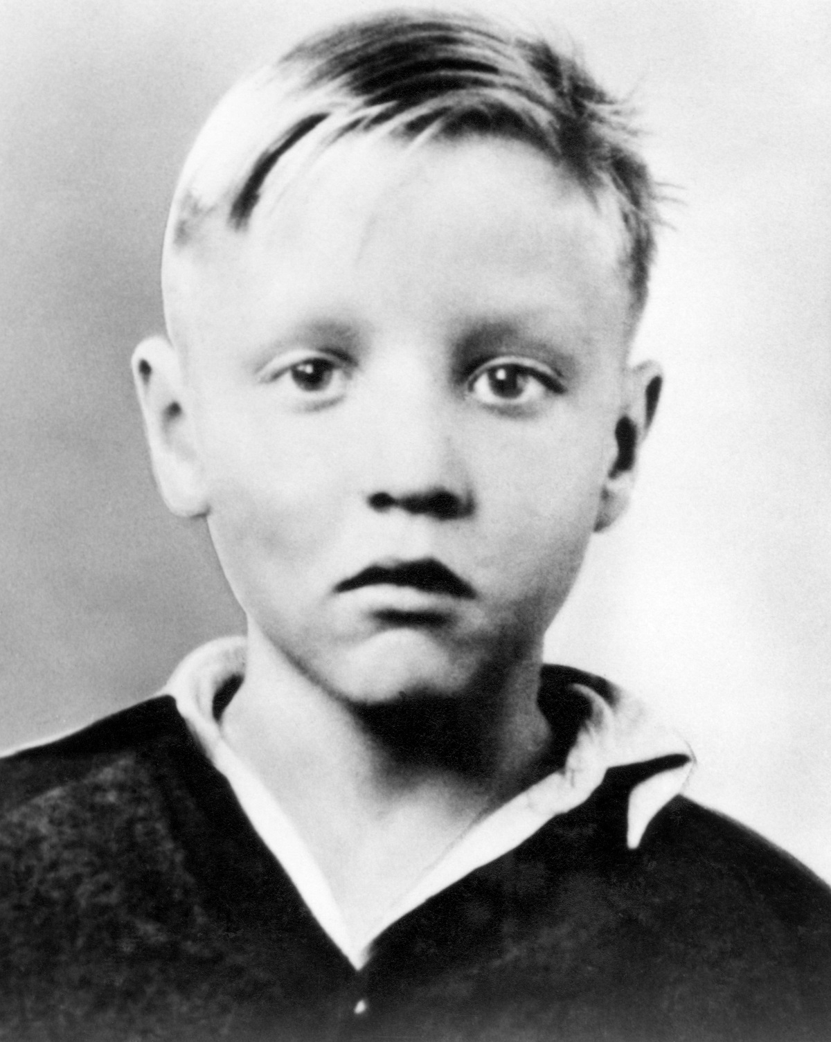 A headshot of a blonde Elvis Presley as a child in the early 1940s