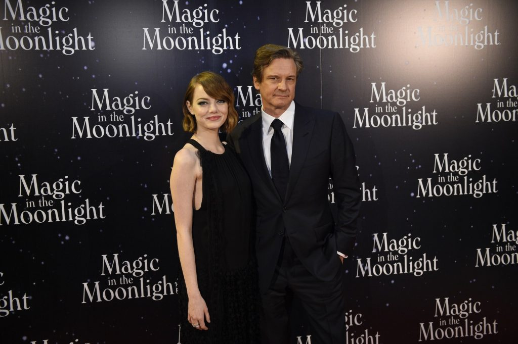 (L-R) Emma Stone and Colin Firth smiling in front of a black background with repeating logos