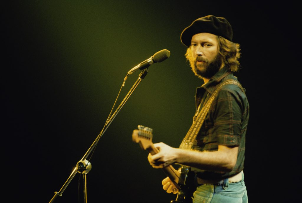 British guitarist Eric Clapton performing on stage during his US tour, July 1975. He's on stage holding a guitar and staring to his left, wearing denims, a black shirt and a black hat.