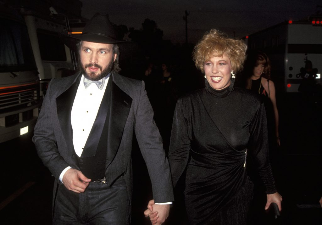 Garth Brooks and wife Sandy Mahl walking hand in hand at an awards show