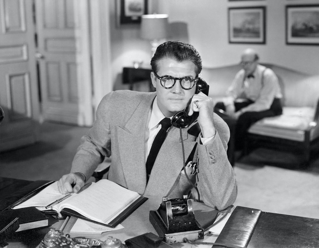 George Reeves as Clark Kent in 'The Adventures of Superman', posed using a phone, in black and white