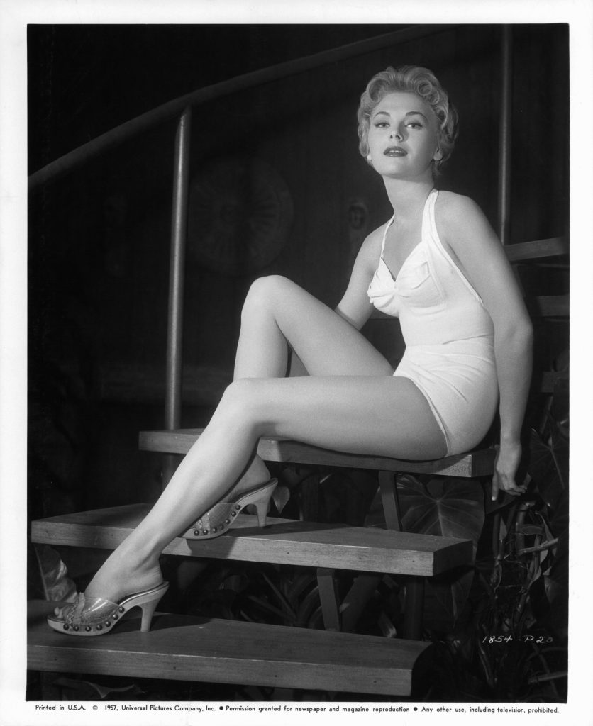 Joanna Moore poses in a white swimsuit for a 1957 promotional poster for the film 'Slim Carter'