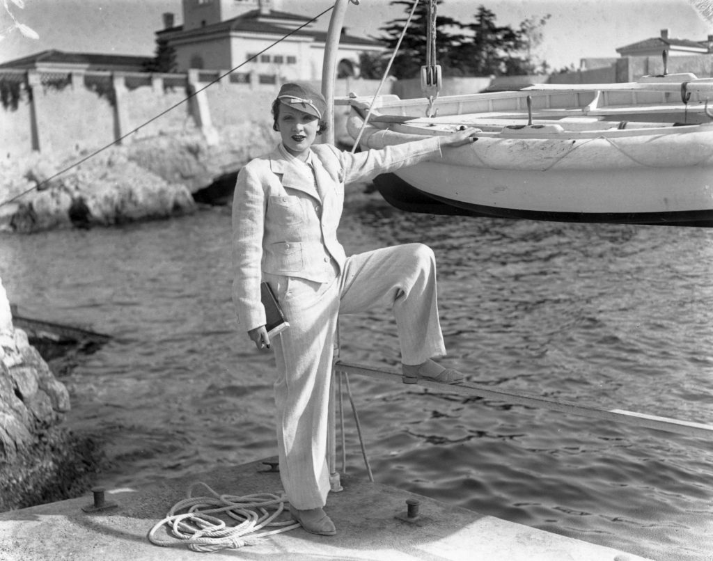 Marlene Dietrich in a pantsuit standing next to a waterfront, in black and white