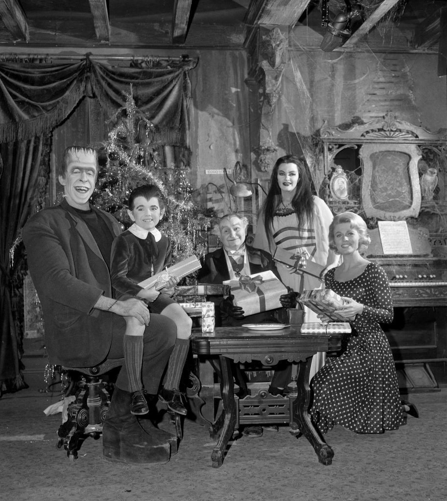 Fred Gwynne as Herman Munster, Butch Patrick as Eddie Munster, Al Lewis as Grandpa Munster, Yvonne DeCarlo as Lily Munster, and Pat Priest as Marilyn Munster in a cast photo of 'The Munsters', 1964