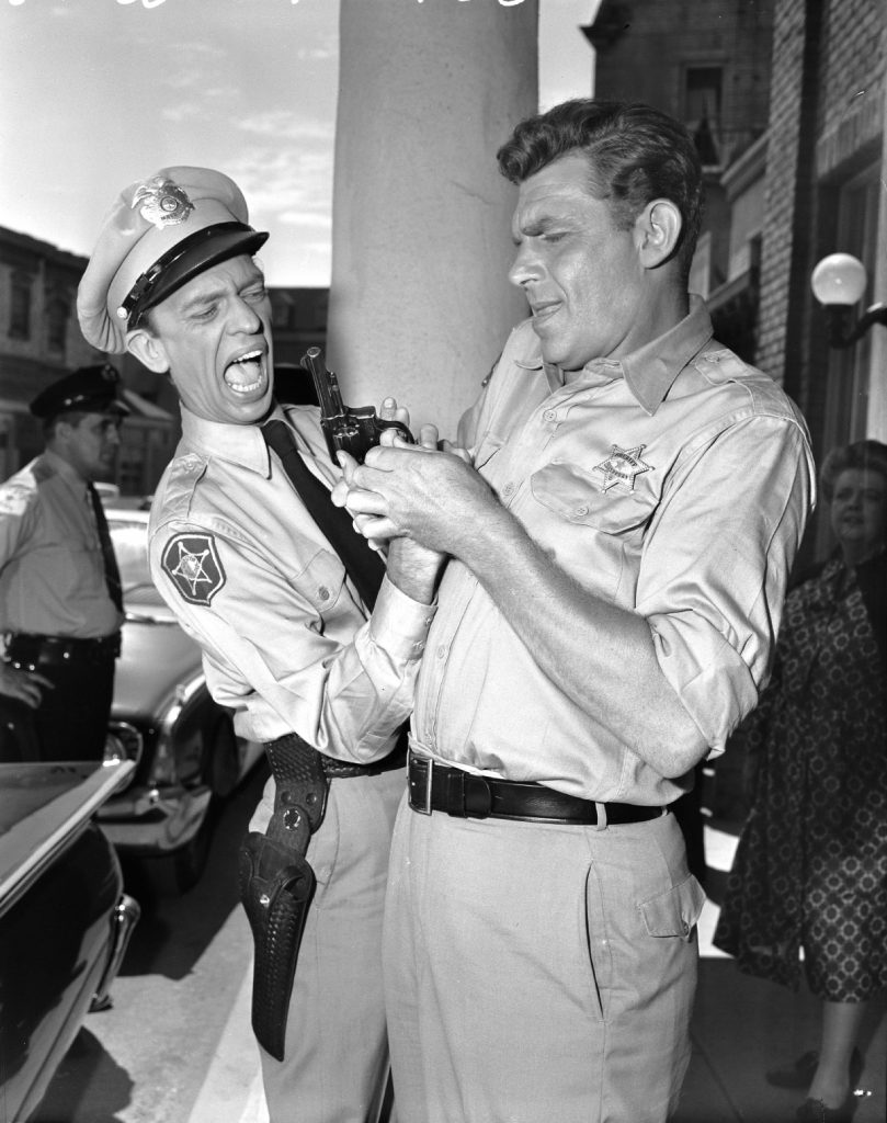 Don Knotts as Barney Fife and Andy Griffith as Sheriff Andy Taylor fumble over a gun in a scene from 'The Andy Griffith Show,' 1960