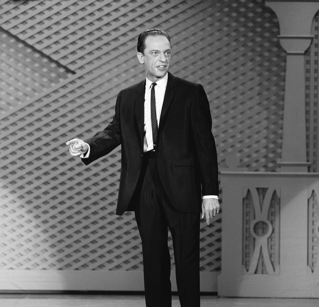 Television actor Don Knotts dressed in a suit and tie addressing an audience, 1965