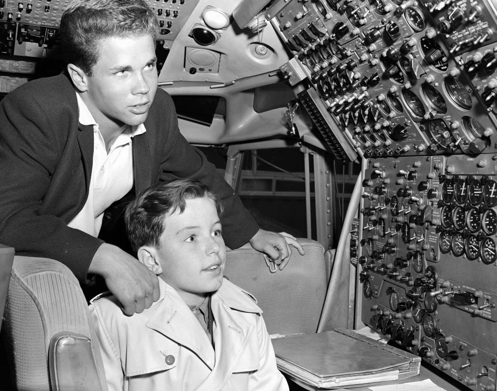 Tony Dow stands behind Jerry Mathers as he sits in a chair in the cockpit of an airplane