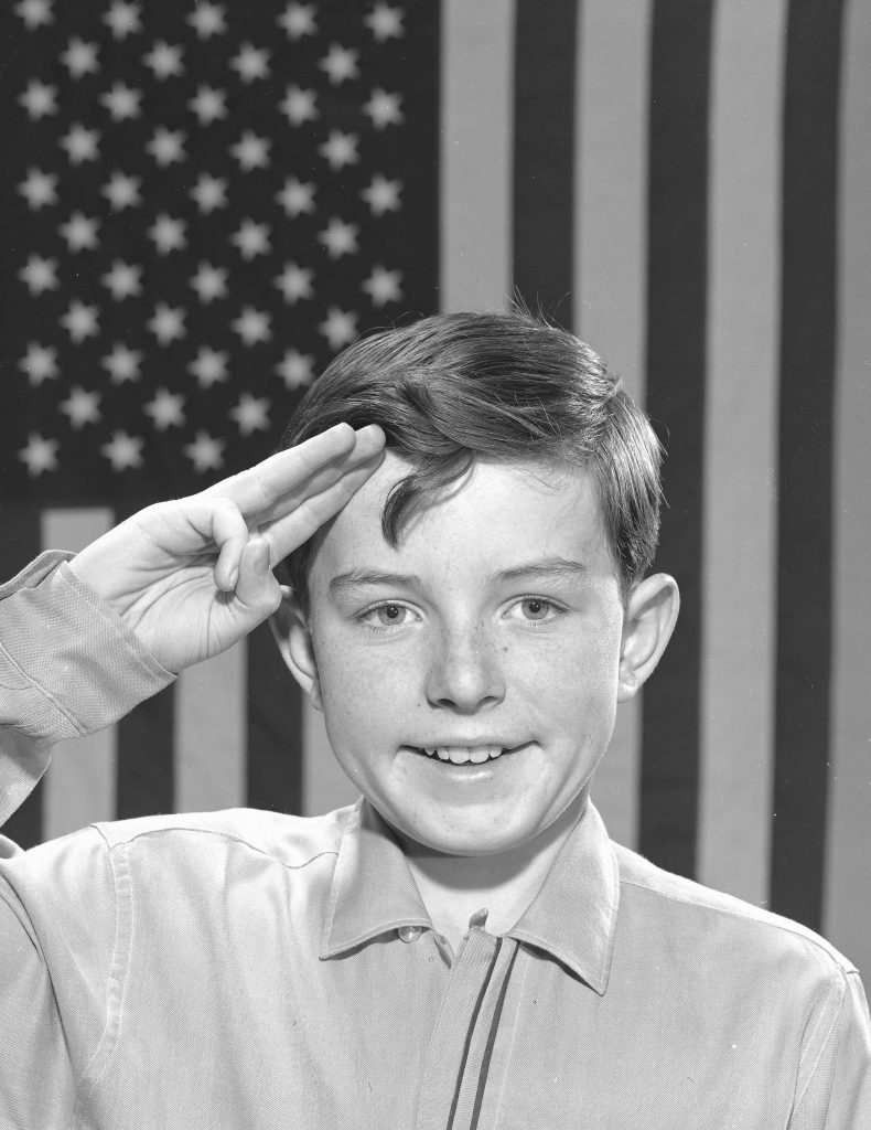 'Leave It to Beaver' star Jerry Mathers saluting the flag, 1961