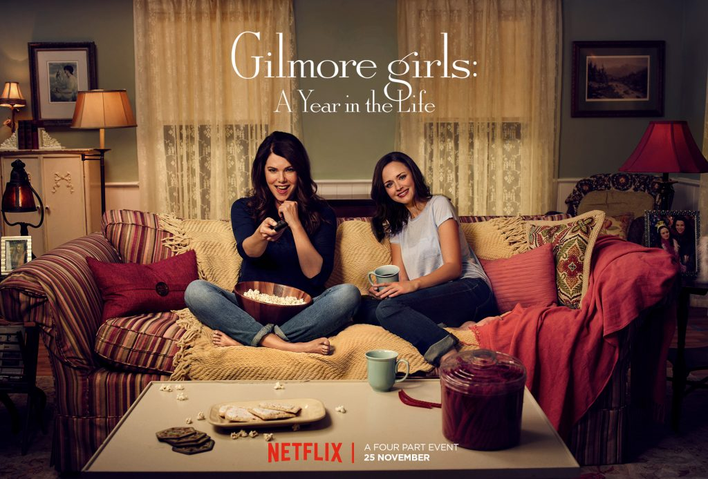 Lauren Graham and Alexis Bledel sit on a couch together in a promotional poster for 'Gilmore Girls; A Year in the Life'