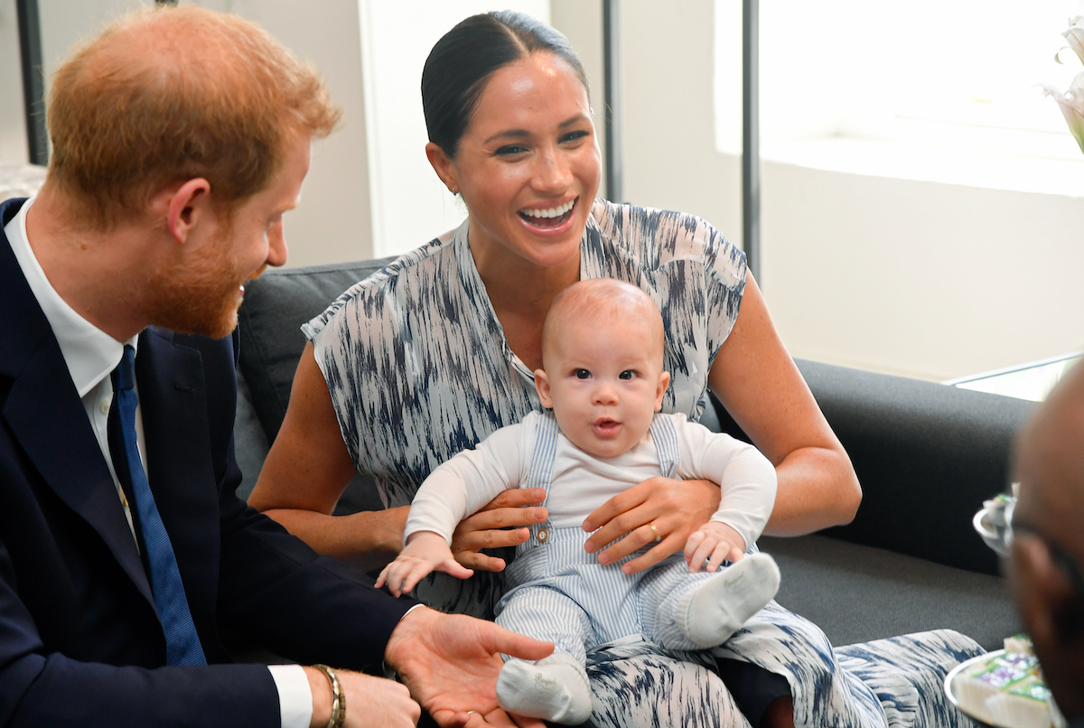Prince Harry and Meghan Markle smile while son, Archie, sits on Meghan's lap